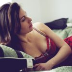 Woman in red lingerie lays on bed