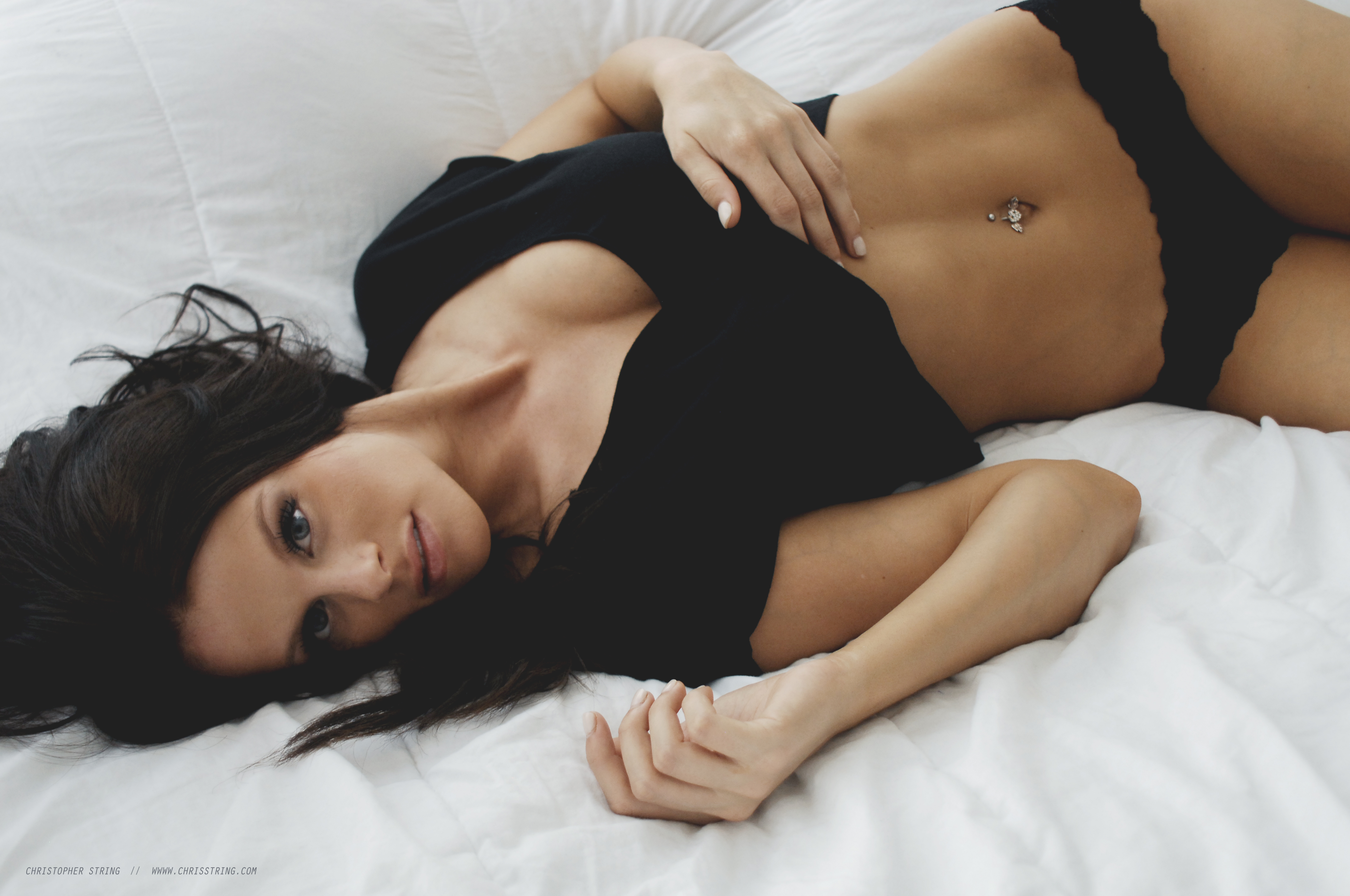Woman in black top and underwear on white sheets